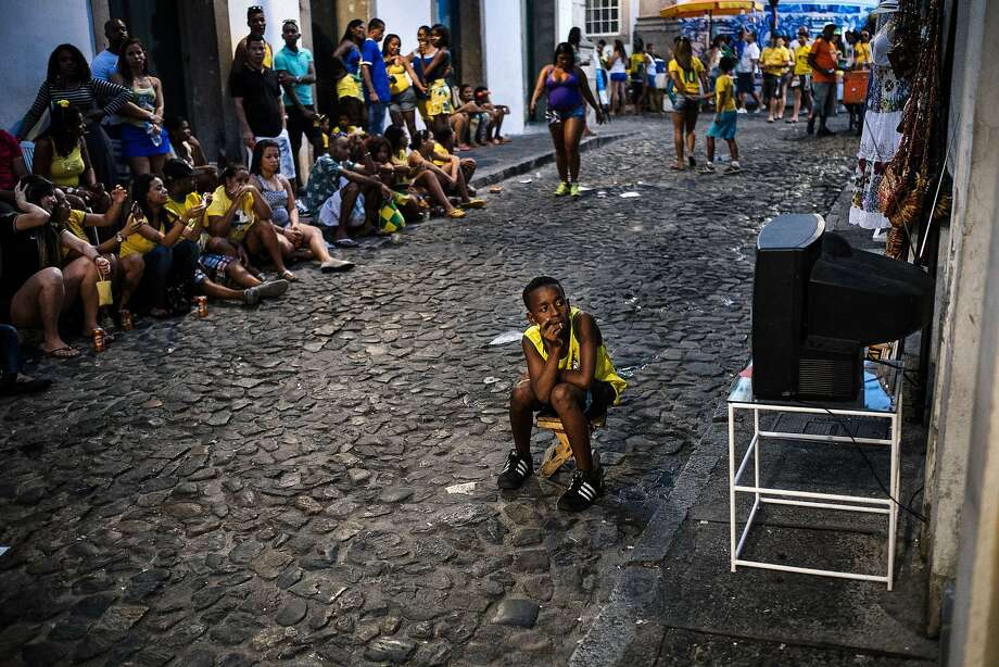 How Brazil watches the World Cup: An alley in Salvador becomes an open-air theater to follow the host team's exploits on TV. Photo: Dimitar Dilkoff, AFP/Getty Images
