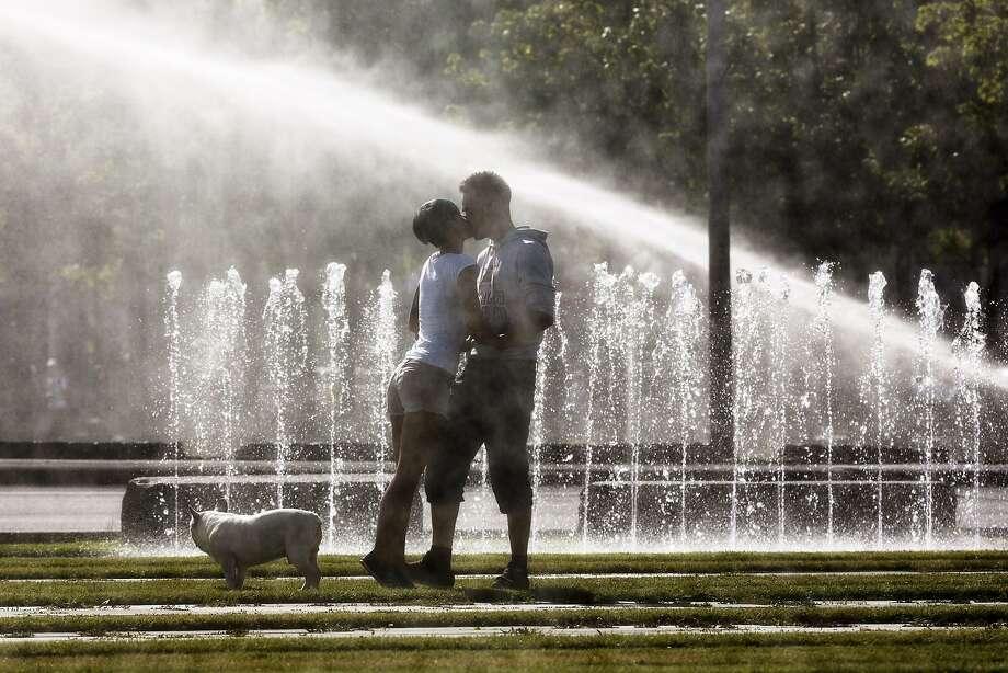 An overheated coupletakes a cold shower in Berlin. Photo: Markus Schreiber, Associated Press