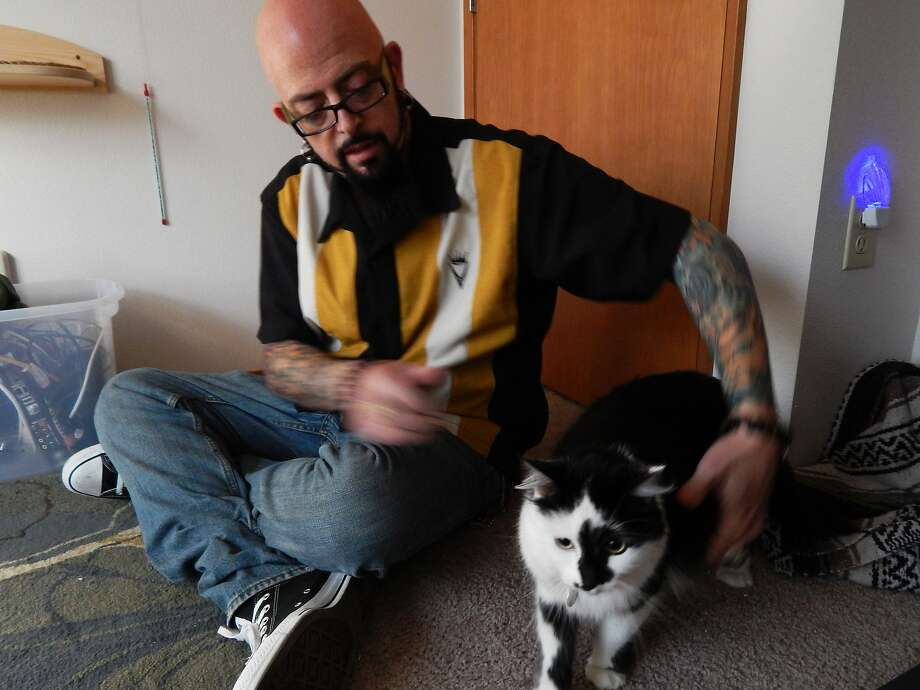 "Galaxy's 'hardest' case: Feline behaviorist Jackson Galaxy, host of Animal Planet's ""My Cat From Hell,"" pets Lux, the cat who became notorious for attacking his owner's child and chasing the entire family into a bedroom, forcing the owner to call 9-1-1. Lux's episode on ""My Cat"" ends in a cliffhanger. Photo: Animal Planet, Associated Press"