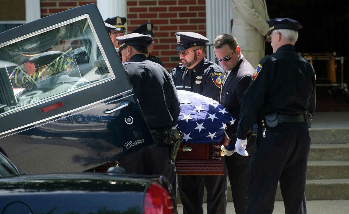 Members of the Stamford Police Department serve as pallbearers for the funeral of former Police Chief Louis DeCarlo at Sacred Heart Roman Catholic Church in Stamford, Conn., on Wednesday, June 18, 2014. Pallbearers were, clockwise from left, Sgt. Anthony Lupinacci, Officer Ed Rondano, Cpt. Gregory Tomlin, Officer Cory Casserta, Sgt. Peter di Spania, and Sgt. Paul Guzda.