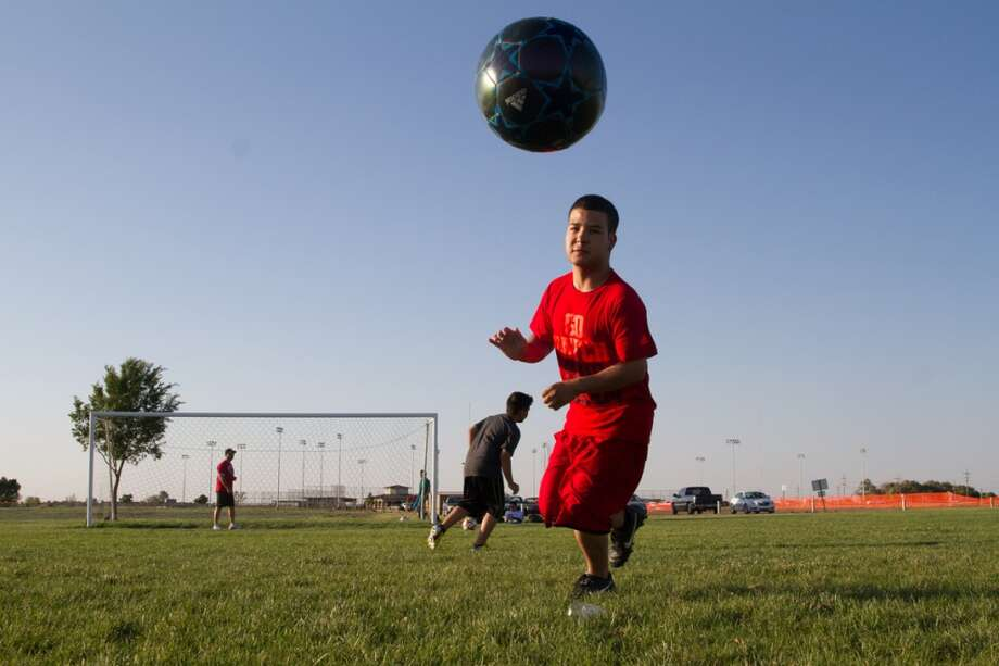 Orlando Palma runs after a soccer ball while warming up to play a game on the soccer fields in Liberal, KS. Photo: Douglas Zimmerman, Courtesy