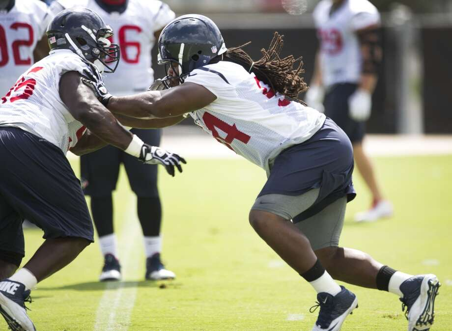 Texans defensive end Tim Jamison, left, and nose tackle Ricardo Mathews run a drill. Photo: Brett Coomer, Houston Chronicle