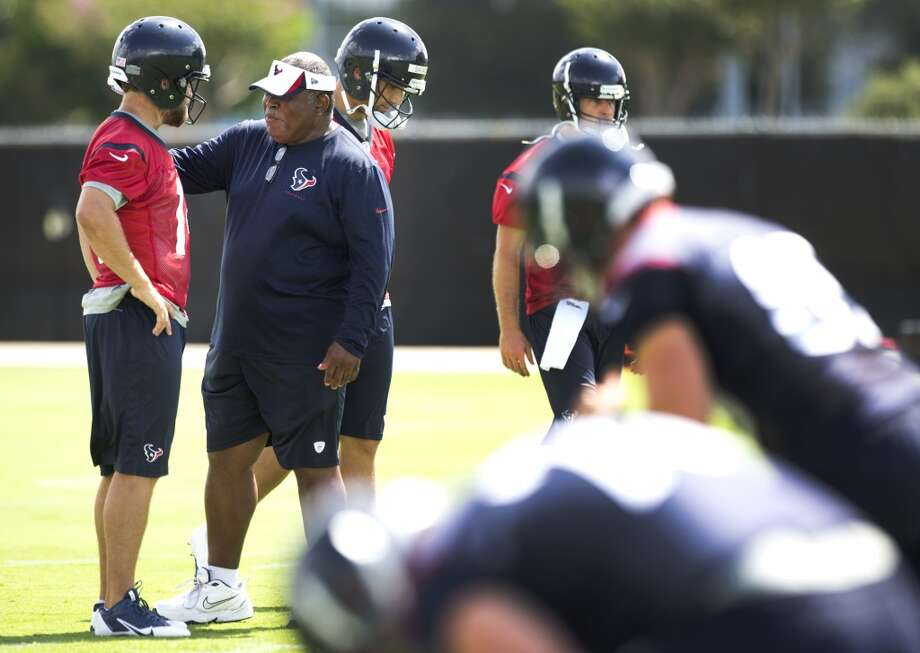 Texans defensive coordinator Romeo Crennell talks to quarterback Ryan Fitzpatrick, far left. Photo: Brett Coomer, Houston Chronicle