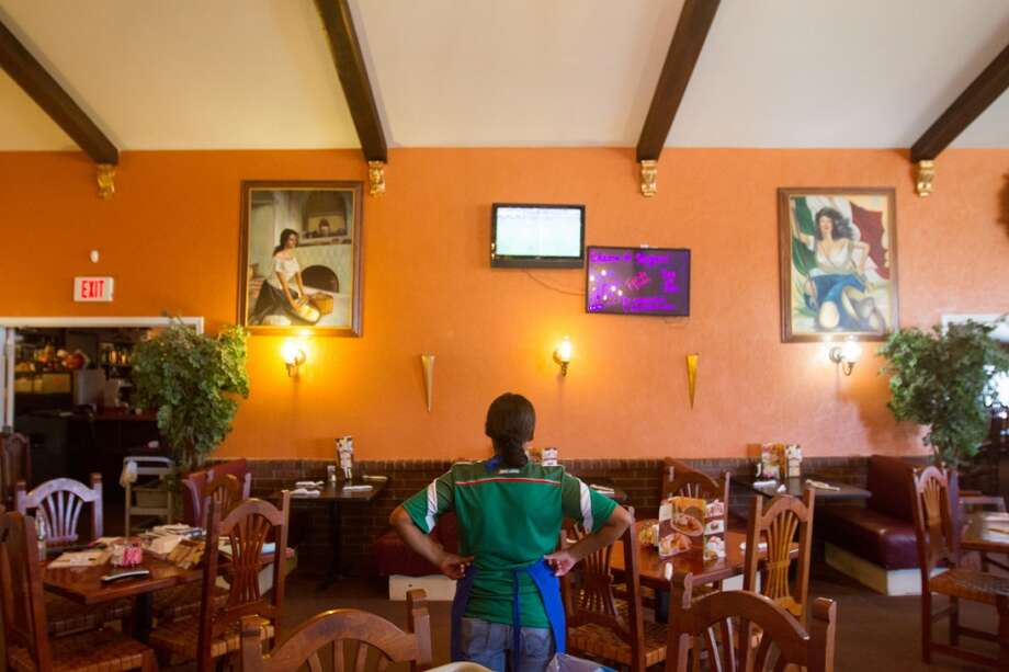 A Mexico soccer fan takes a break from work to watch the Mexico vs. Brazil first round World Cup match at Vargas restaurant in Liberal, KS. Photo: Douglas Zimmerman, Courtesy