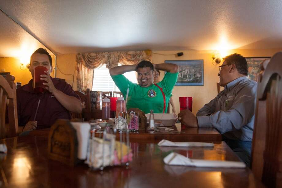 Mexico soccer fans (left to right) Juan Rosales, Javier Rosales, and Gary Andrews watch the Mexico vs. Brazil first round World Cup match at Vargas restaurant in Liberal, KS. Photo: Douglas Zimmerman, Courtesy
