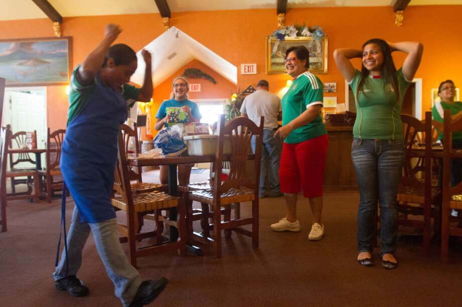 Mexican soccer fans celebrate Mexico's tie with Brazil after watching their first round World Cup match at Vargas restaurant in Liberal, KS. Photo: Douglas Zimmerman, Courtesy