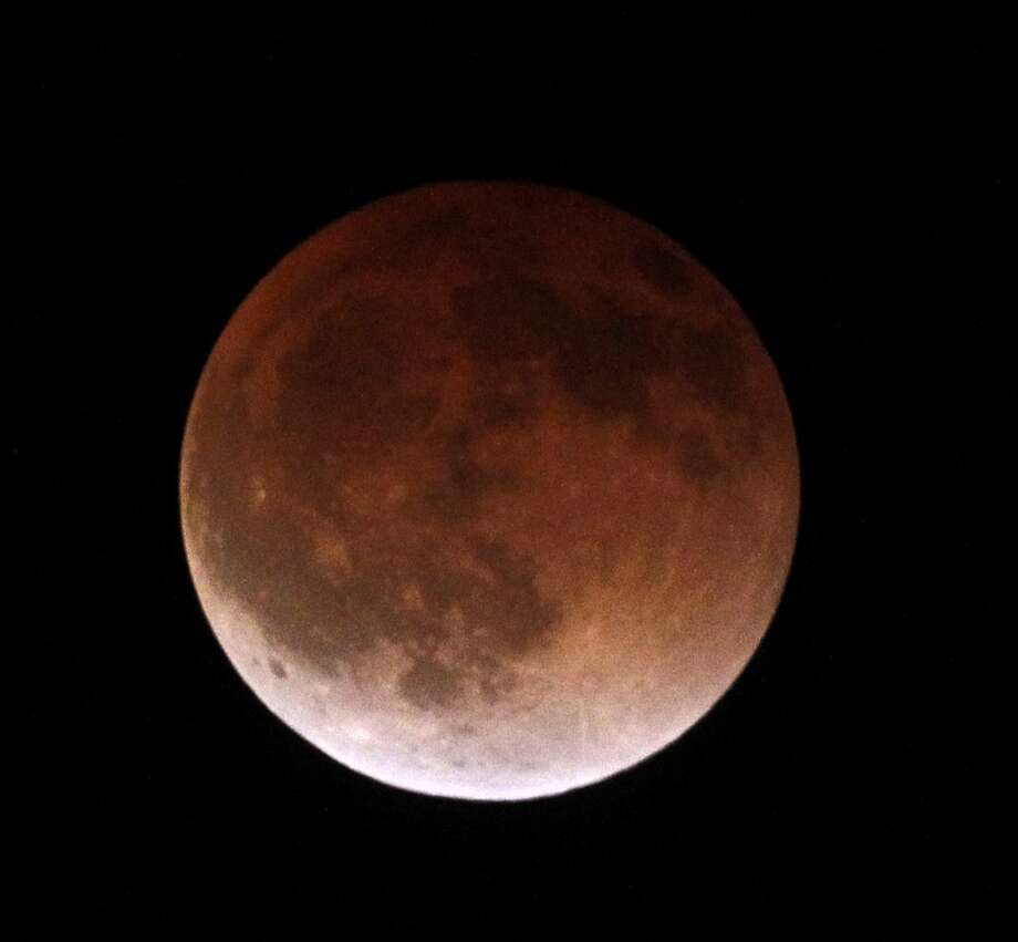 "The moon completely crosses the earth's shadow in a total lunar eclipse, becoming a ""blood moon"" because of sunlight bending through Earth's atmosphere and hitting the moon.  Photo: Nick Ut, ASSOCIATED PRESS"
