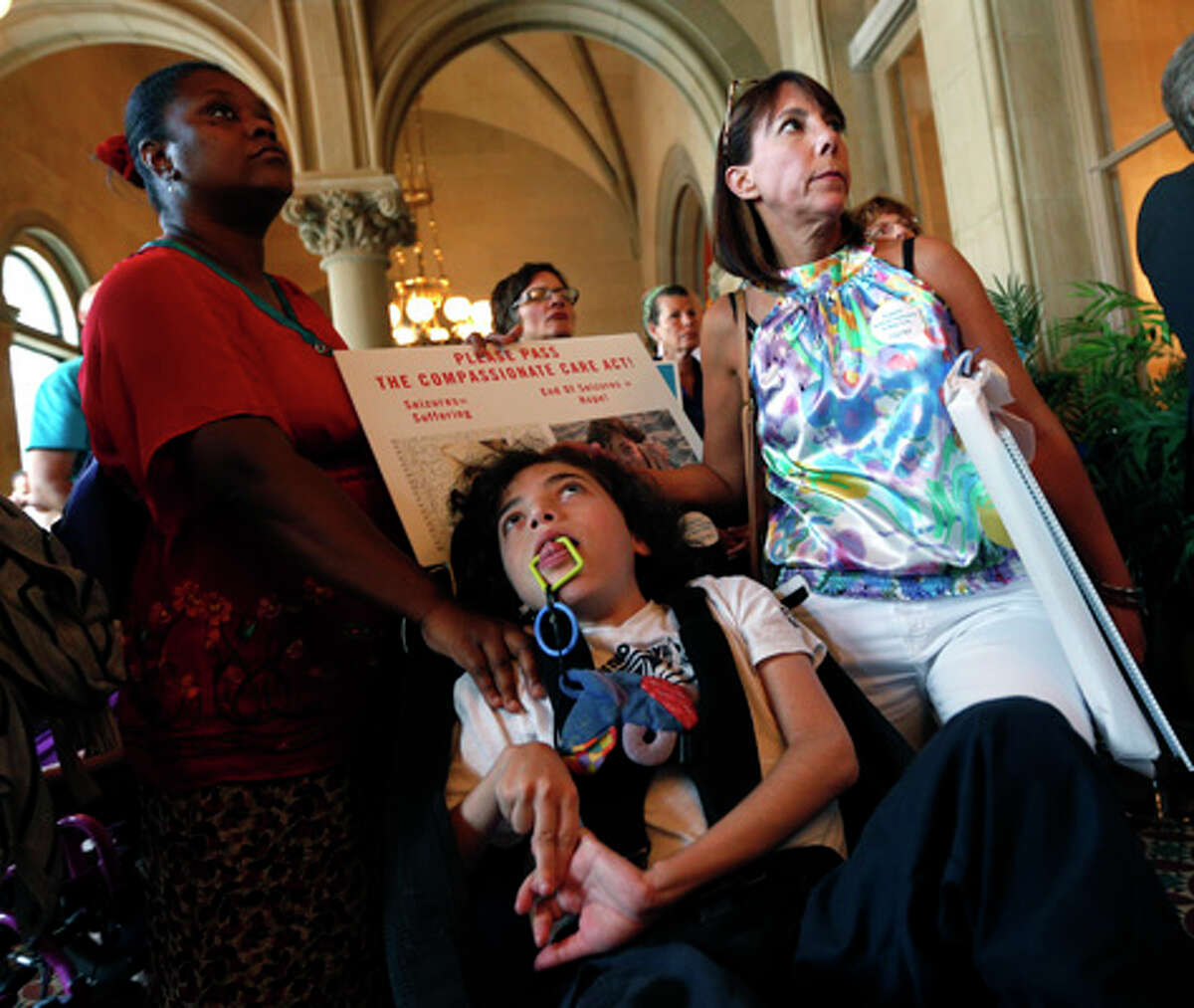 Oliver Miller, 14, center, with his mother Missy Miller, right, and nurse Sandra Sanon during a rally in support of medical marijuana at the Capitol on Wednesday, June 18, 2014, in Albany, N.Y. Dozens of advocates for legalizing medical marijuana are blaming Gov. Andrew Cuomo for stalling the so-called