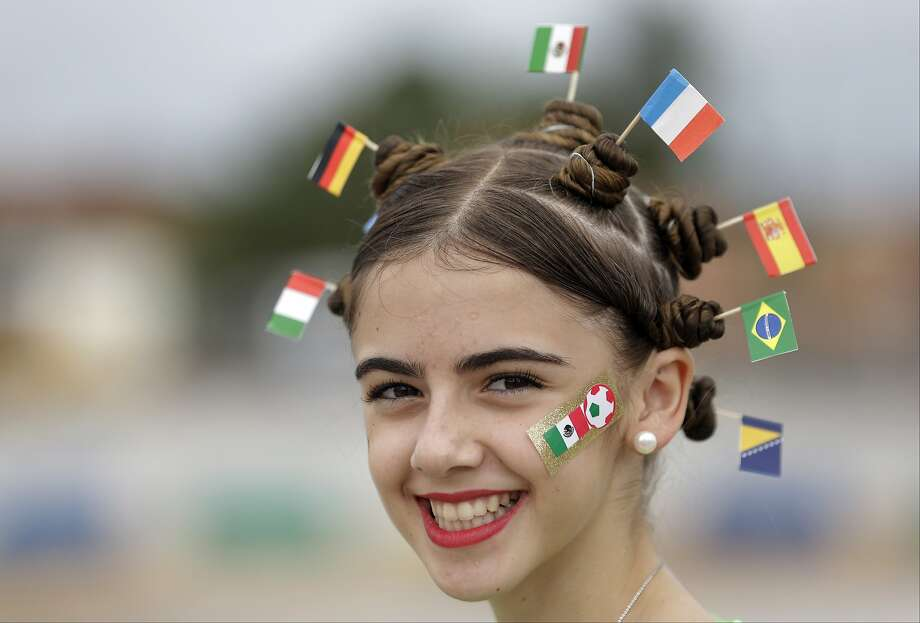 With all the flags in her World Cup coif, it's hard to tell who she's rooting for in Fortaleza, Brazil. (Mexico, apparently.) Photo: Themba Hadebe, Associated Press