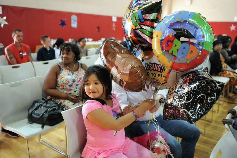 Alexis Marie Obidos, 7, center, holds balloons to give her sister, Ashley Mae Obidos, who was graduating from sixth grade on Wednesday, June 18, 2014, at Pine Hills Elementary in Albany, N.Y. (Cindy Schultz / Times Union) Photo: Cindy Schultz / 00027396A