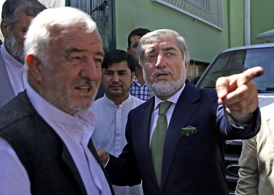 Afghanistan's presidential candidate Abdullah Abdullah, right, leaves after a news conference in Kabul, Afghanistan, Wednesday, June 18, 2014. The front-runner in Afghanistan's runoff presidential election has called for vote counting to stop over fraud claims. (AP Photo/Massoud Hossaini) Photo: Massoud Hossaini, Associated Press