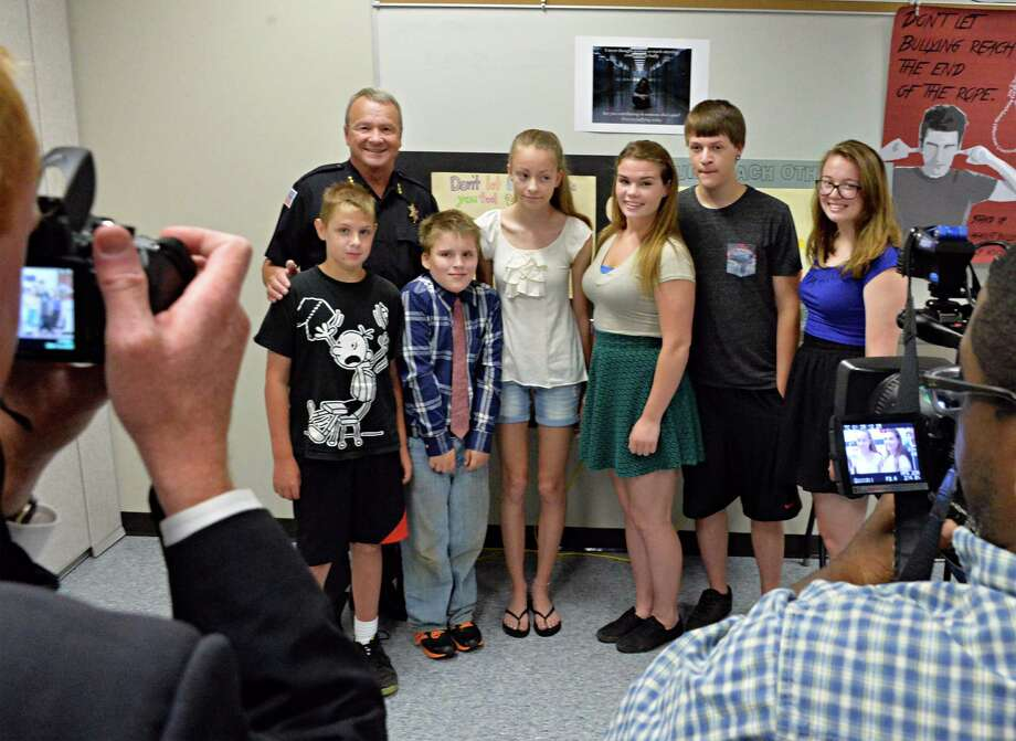 Rensselaer County Sheriff Jack Mahar poses with first place Anti-Bullying poster winners, from left,  Ethan Shults,11, Blake Fox-Schreiber, 10, and Katya Cyrulik, 12, -- of Green Meadow Elementary School in East Greenbush -- and Berlin High School students Jodi Thomas, 18, Hunter Hendricks, 18, and Katie Gallucci during an award ceremony at the Rensselaer County Sheriff's Offices Wednesday June 18, 2014, in Troy, NY. Their artwork will be displayed on the side of CDTA buses.   (John Carl D'Annibale / Times Union) Photo: John Carl D'Annibale / 00027400A