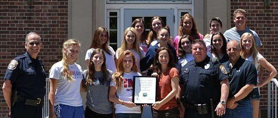 Members of Positive Directions, the Teen Awareness Group and Westport police pose at police headquarters where they collaborated to install a permanent collection box for unwanted or outdated prescription drugs. Photo: Contributed Photo / Westport News