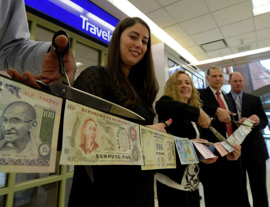 Maria Brusilovsky, marketing for North America for Travelex Currency Exchange, left, makes the cut in a string of canceled currency Wednesday morning, June 18, 2014, to officially open the Travelex Currency Exchange store at Albany International Airport in Colonie, N.Y.  With Brusilovsky are: Claudia Parisi, sales manager for Travelex, second from left, John O'Donnell, CEO Albany International Airport, second from right and John Delbalso, assistant airport manager, right.  (Skip Dickstein / Times Union) Photo: SKIP DICKSTEIN / 00027402A