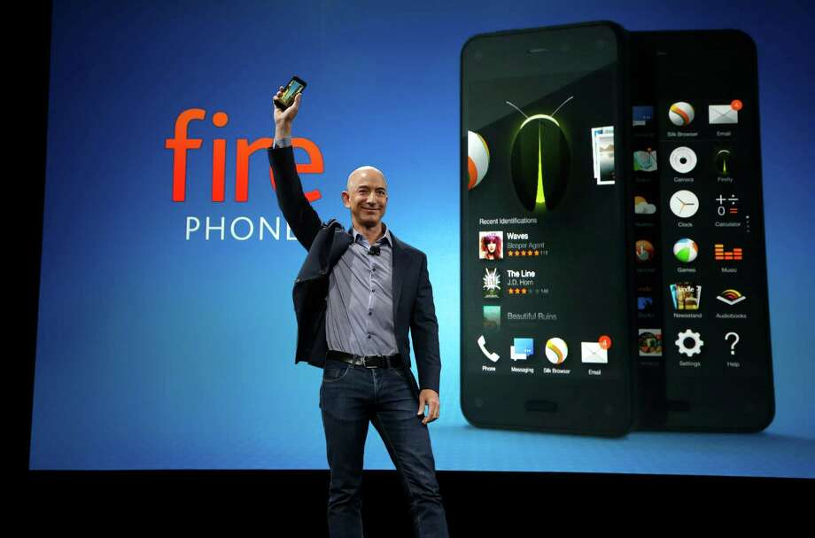 Amazon CEO Jeff Bezos holds up the new Amazon Fire Phone at a launch event, Wednesday, June 18, 2014, in Seattle. (AP Photo/Ted S. Warren) ORG XMIT: WATW101 Photo: Ted S. Warren / AP