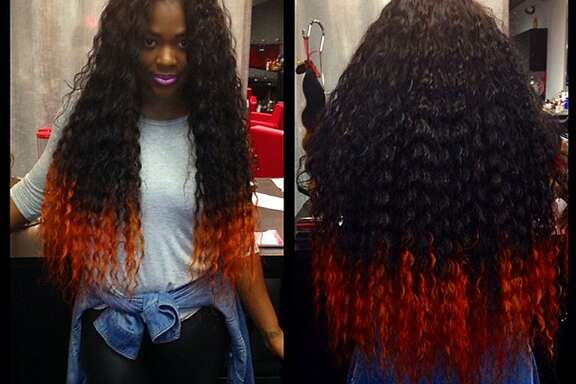 In this undated image provided by Miranda Jade Plater and posted in April 2014 to the Instagram account of her company, Limelight Extensions, Plater poses wearing long, black curly hair extensions with the ends dyed bright orange at her salon in Farmington Hills, Mich. This photo alone has generated about $10,000 in sales. (AP Photo/Courtesy Miranda Jade Plater)