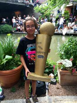 Mercedes, 9, wields a replica championship trophy her aunt made while she waits for the River Walk parade to start on Wednesday, June 18, 2014. Photo: Rebecca Fiedler/San Antonio Express-News