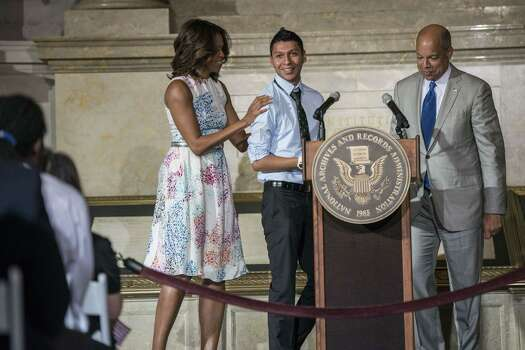 US First Lady Michelle Obama (L) and US Secretary of Homeland Security Jeh Johnson (R) stand with newly sworn in US citizen Juan Cue Monroy, 20 born in Guatemala, during a naturalization ceremony at the National Archives June 18, 2014 in Washington, DC. Fifty new citizens were sworn in during the event. AFP PHOTO/Brendan SMIALOWSKIBRENDAN SMIALOWSKI/AFP/Getty Images Photo: BRENDAN SMIALOWSKI, AFP/Getty Images / AFP