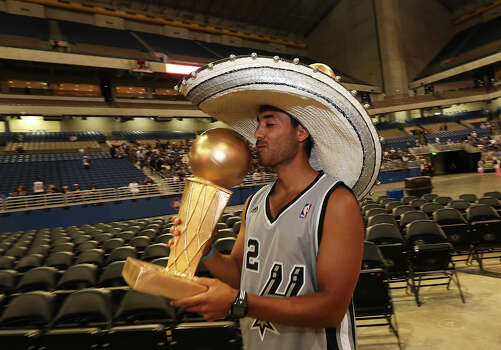 San Antonio Spurs fan Jeremy Alvarez, 22, of Corpus Christi kisses a fake Larry O'Brien Championship trophy at the Alamodome, Wednesday, June 18, 2014. The Spurs beat the Miami Heat in the NBA Finals on Sunday. The celebration will start with a River Parade and end at the Alamodome. Photo: Jerry Lara, San Antonio Express-News / ©2014 San Antonio Express-News