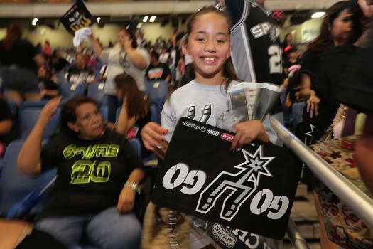 San Antonio Spurs fan Mercedez Diaz, 11, rushes to get prime seats at the Alamodome for the Championship Celebration, Wednesday, June 18, 2014. The Spurs beat the Miami Heat in the NBA Finals on Sunday. The celebration will start with a River Parade and end at the Alamodome. Diaz was celebrating her birthday at the dome. Photo: Jerry Lara, San Antonio Express-News / ©2014 San Antonio Express-News
