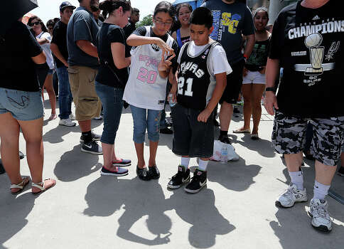 San Antonio Spurs fans Celeste Olivares, 10, and her cousin, Raj Chavarria 10, make shadow figures as they wait to enter the Alamodome for the Championship Celebration, Wednesday, June 18, 2014. The Spurs beat the Miami Heat in the NBA Finals on Sunday. The celebration will start with a River Parade and end at the Alamodome. Photo: Jerry Lara, San Antonio Express-News / ©2014 San Antonio Express-News