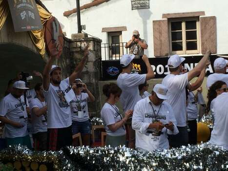 Spurs player Marco Belinelli waves to the crowd from a float with Matt Bonner and Aron Baynes (turned away) during the Spurs victory river parade on Wednesday, June 18, 2014. Photo: Mitchell Ferman / San Antonio Express-News