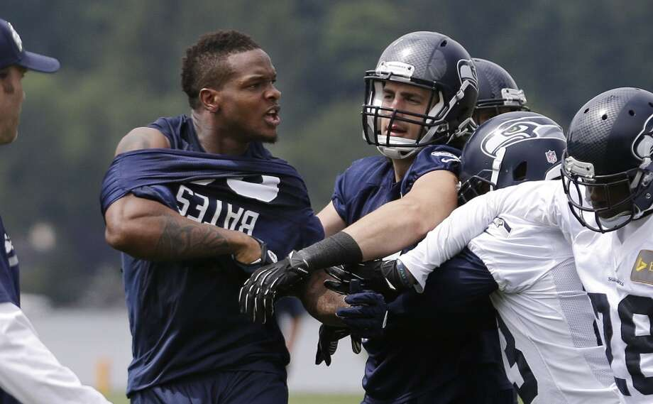 Seahawks receiver Phil Bates, left, is led away by teammates from a scuffle that left him with his jersey nearly pulled-off during minicamp practice Wednesday in Renton. Photo: Elaine Thompson, Associated Press