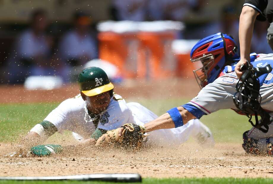 Yoenis Céspedes slides home ahead of Robinson Chirinos' tag in the fifth inning of the A's 4-2 win over Texas on Wednesday. Photo: Thearon W. Henderson, Getty Images