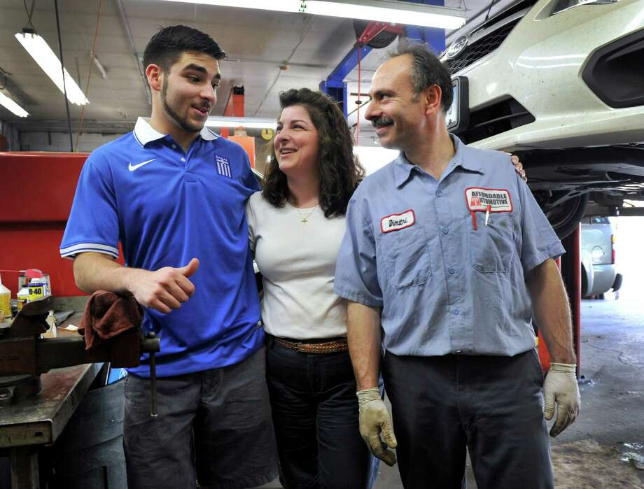 The Koulouris family, owners of Affordable Automotive in New Milford, Conn., huge soccer fans, are following the World Cup games closely. From left are Yianni, 19, wearing the shirt of the team, and parents Rose, 44, and Dimitri Koulouris, 50, Wednesday, June 18, 2014. Photo: Carol Kaliff / The News-Times