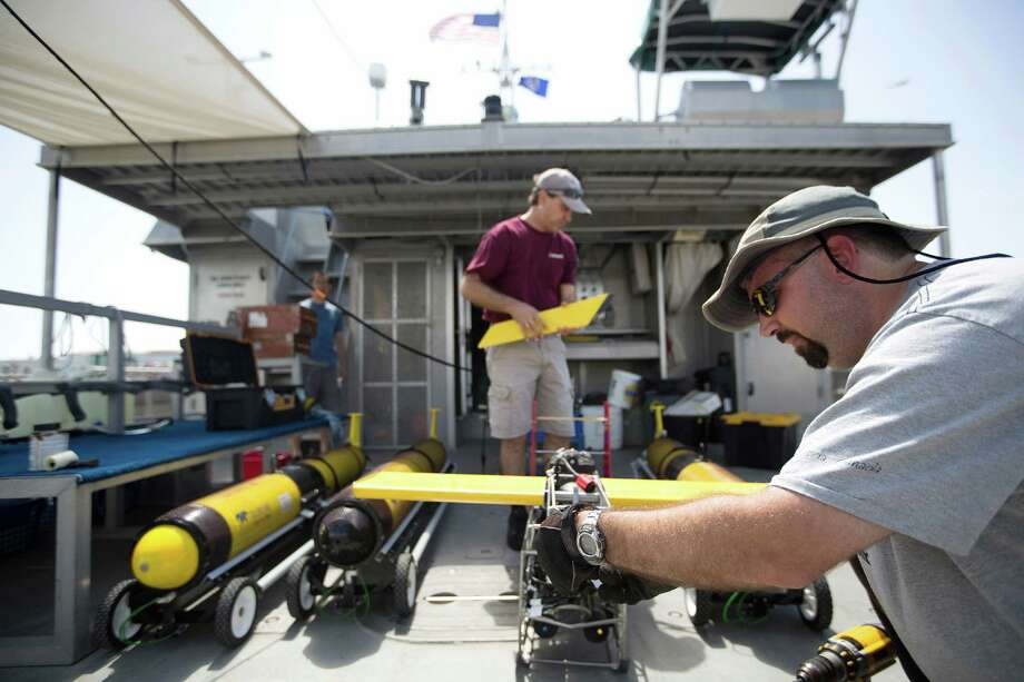 Marine technician Andrew Dancer, right, and Steve DiMarco, a Texas A&M ocean-ography professor, work on an Acrobat towed underwater vehicle Photo: Johnny Hanson, Staff / © 2014  Houston Chronicle