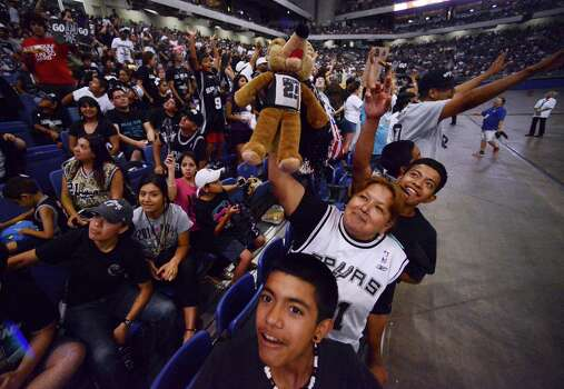 Fabian Alvarez, front, and his mother, Irma Alvarez, cheer during a celebration of the Spurs' fifth NBA championship on Wednesday, June 18, 2014, in the Alamodome. Photo: Billy Calzada, San Antonio Express-News / San Antonio Express-News