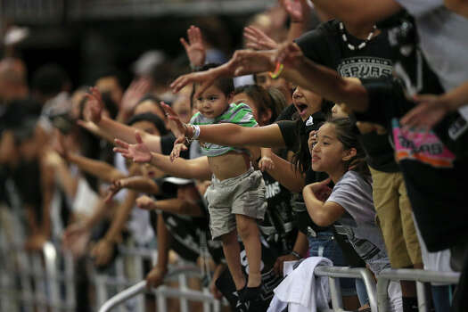 A San Antonio Spurs fan holds her toddler out while others reach out for free t-shirts at the Alamodome for the Championship Celebration, Wednesday, June 18, 2014. The Spurs beat the Miami Heat in the NBA Finals on Sunday. The celebration will start with a River Parade and end at the Alamodome. Photo: Jerry Lara, San Antonio Express-News / ©2014 San Antonio Express-News