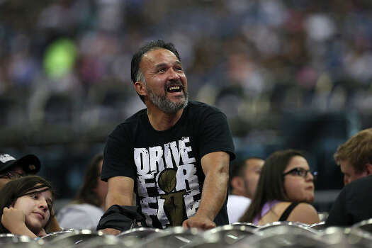San Antonio Spurs fan Domingo Avila, Jr, 50, reacts as the image of Tim Duncan appears on a live-telecast monitor at the Alamodome before the Championship Celebration, Wednesday, June 18, 2014. Duncan was on a barge at the River Parade before the Alamodome celebration. The Spurs beat the Miami Heat to claim the NBA Championship title. Photo: Jerry Lara, San Antonio Express-News / ©2014 San Antonio Express-News