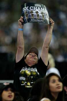 San Antonio Spurs fan Diana Munoz, 46, reacts as the image of Tim Duncan appears on a live-telecast monitor at the Alamodome before the Championship Celebration, Wednesday, June 18, 2014. Duncan was on a barge at the River Parade before the Alamodome celebration. The Spurs beat the Miami Heat to claim the NBA Championship title. Photo: Jerry Lara, San Antonio Express-News / ©2014 San Antonio Express-News