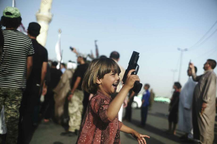 A young Iraqi boy carries a handgun as a militia that was formed to defend the capital parades through the Sadr City neighborhood of Baghdad. Photo: Ayman Oghanna / New York Times / NYTNS