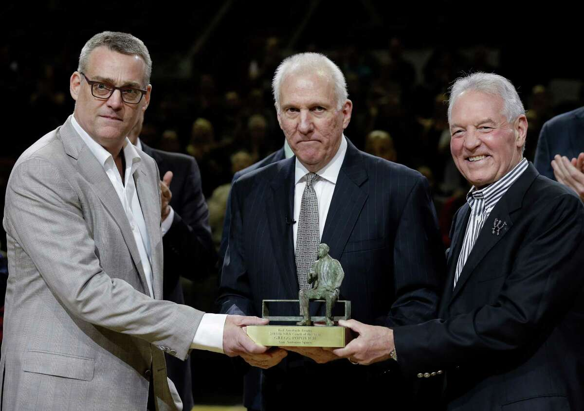 In this Wednesday, April 23, 2014 photo, San Antonio Spurs coach Gregg Popovich, center, stands with general manager R.C.Buford, left, and team owner Peter Holt, as he holds his NBA coach of the year trophy during the first half of Game 2 of the opening-round NBA basketball playoff series, in San Antonio. Buford has been named NBA Executive of the Year. (AP Photo/Eric Gay, File)