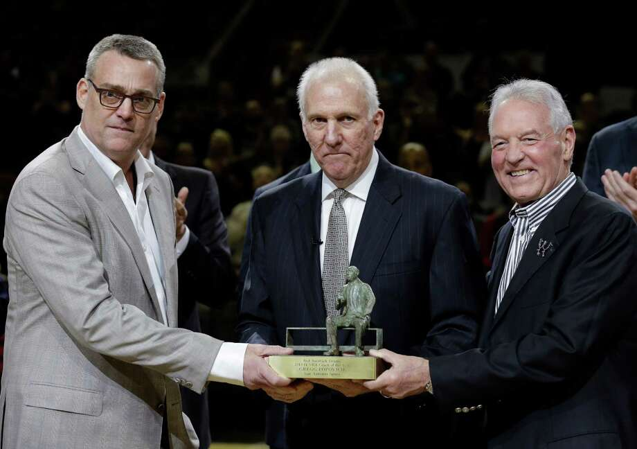 In this Wednesday, April 23, 2014 photo, San Antonio Spurs coach Gregg Popovich, center, stands with general manager R.C.Buford, left, and team owner Peter Holt, as he holds his NBA coach of the year trophy during the first half of Game 2 of the opening-round NBA basketball playoff series, in San Antonio. Buford has been named NBA Executive of the Year. (AP Photo/Eric Gay, File) Photo: Eric Gay, Associated Press / AP