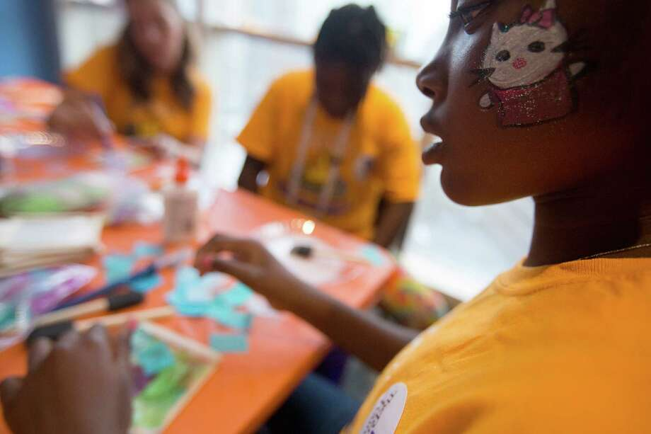 There for her cousin's treatment, Jakayla Brown, 10, does an art project after having her face painted while patients and their families at Texas Children's Hospital Cancer and Hematology Center participated in the Camp Periwinkle Day at Texas Children's Hospital Wednesday, June 18, 2014, in Houston.  Photo: Johnny Hanson, Houston Chronicle / © 2014  Houston Chronicle