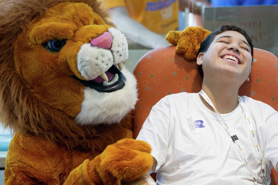 The Spring High School mascot sneaks up on patient Isaiah Mendoza, 15, who is being treated for leukemia, as patients and their family members at Texas Children's Hospital Cancer and Hematology Center participated in the Camp Periwinkle Day at Texas Children's Hospital Wednesday, June 18, 2014, in Houston. The Periwinkle Foundation, with the support of BG Group, brought two days activities, circus-themed games and fun to the outpatient and inpatient children and young adults under care at Texas Children's Cancer Center and Hematology Centers.