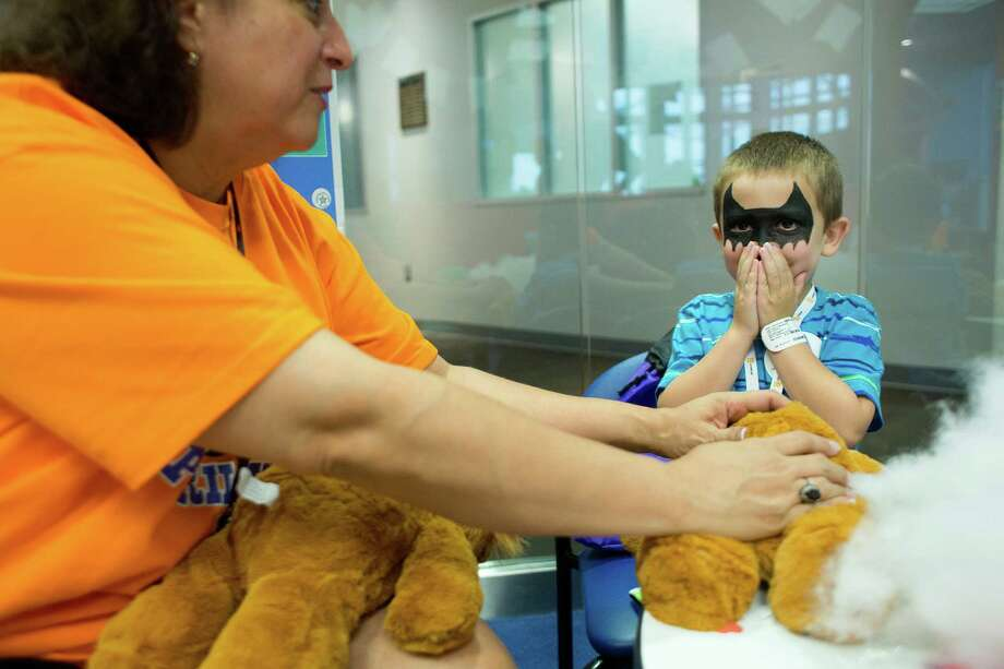 Before placing a small heart into his new stuffed lion, Dalton Lee, 5, of Beach City, makes a wish next to volunteer, Saundra Gussman with the BG Group, as patients at Texas Children's Hospital Cancer and Hematology Center participated in the Camp Periwinkle Day at Texas Children's Hospital Wednesday, June 18, 2014, in Houston. Dalton is in remission from T-cell lymphoma, which he was diagnosed with when he was 10-months-old. Photo: Johnny Hanson, Houston Chronicle / © 2014  Houston Chronicle