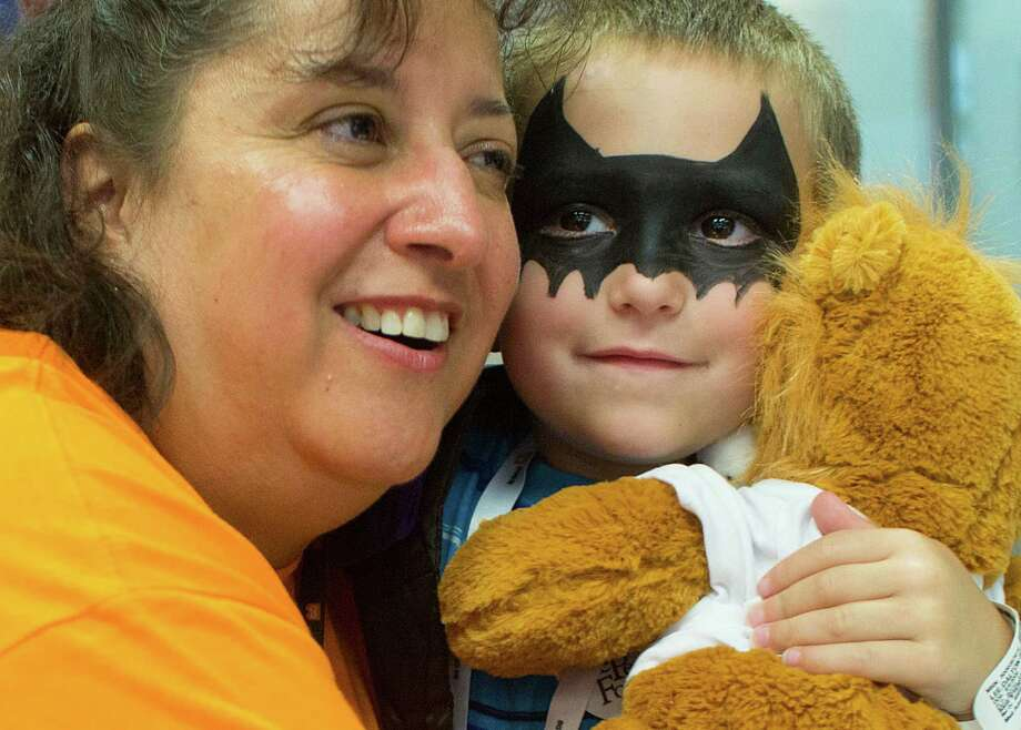 After building his own stuffed lion, Dalton Lee, 5, of Beach City, gets a hug from volunteer, Saundra Gussman with the BG Group, as patients at Texas Children's Hospital Cancer and Hematology Center participated in the Camp Periwinkle Day at Texas Children's Hospital Wednesday, June 18, 2014, in Houston. Dalton is in remission from T-cell lymphoma, which he was diagnosed with when he was 10-months-old.  Photo: Johnny Hanson, Houston Chronicle / © 2014  Houston Chronicle