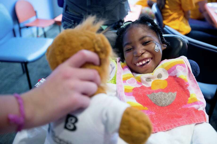 Volunteer Madison Langley, played with a stuffed lion with patient Ellenore Hafford, 7, who was being treated for sickle cell anemia as patients and their family members at Texas Children's Hospital Cancer and Hematology Center participated in the Camp Periwinkle Day at Texas Children's Hospital Wednesday, June 18, 2014, in Houston. Photo: Johnny Hanson, Houston Chronicle / © 2014  Houston Chronicle