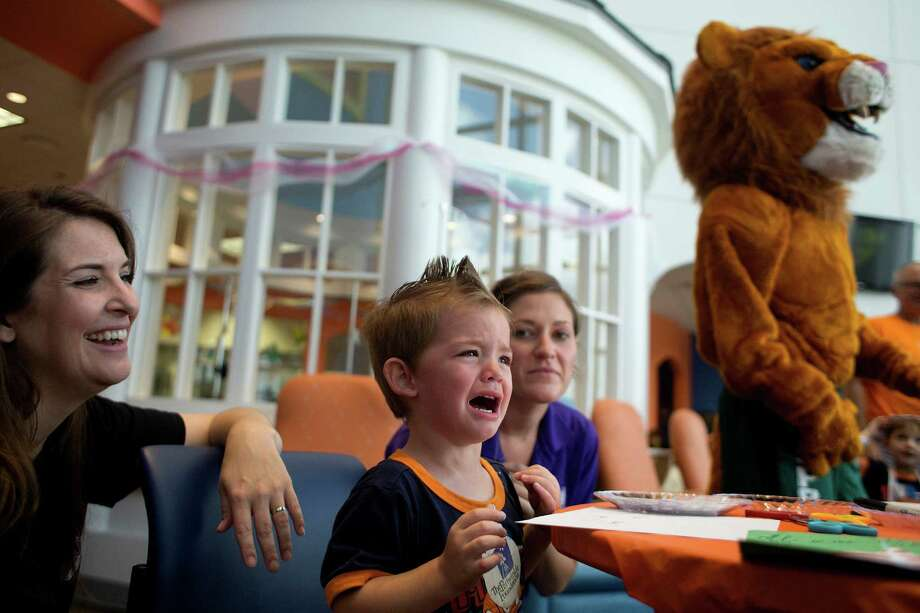 There for his brother's treatment, Gavin Garnett, 2, cries next to his mother Jennifer from Victoria after Gavin caught sight of the Spring High School mascot lion as patients and their family members at Texas Children's Hospital Cancer and Hematology Center participated in the Camp Periwinkle Day at Texas Children's Hospital Wednesday, June 18, 2014, in Houston.  Photo: Johnny Hanson, Houston Chronicle / © 2014  Houston Chronicle