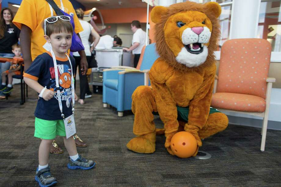 Patient Gage Garnett, 4, of Victoria plays with the Spring High School mascot as patients and their family members at Texas Children's Hospital Cancer and Hematology Center participated in the Camp Periwinkle Day at Texas Children's Hospital Wednesday, June 18, 2014, in Houston.  Photo: Johnny Hanson, Houston Chronicle / © 2014  Houston Chronicle