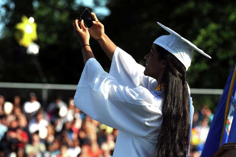 "Salutatorian Haley Arden Mitchell-Adams takes a ""selfie"" during her speach at commencement for the Frank Scott Bunnell High School Class of 2014, in Stratford, Conn. June 18, 2014. Photo: Ned Gerard / Connecticut Post"