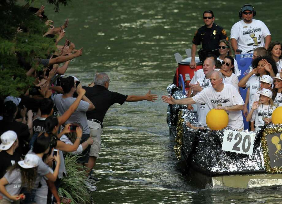 San Antonio Spurs Coach Gregg Popovich reaches to high-five a fan during the river parade on Wednesday, June 18, 2014, on the San Antonio River. Photo: Timothy Tai, San Antonio Express-News / © 2014 San Antonio Express-News