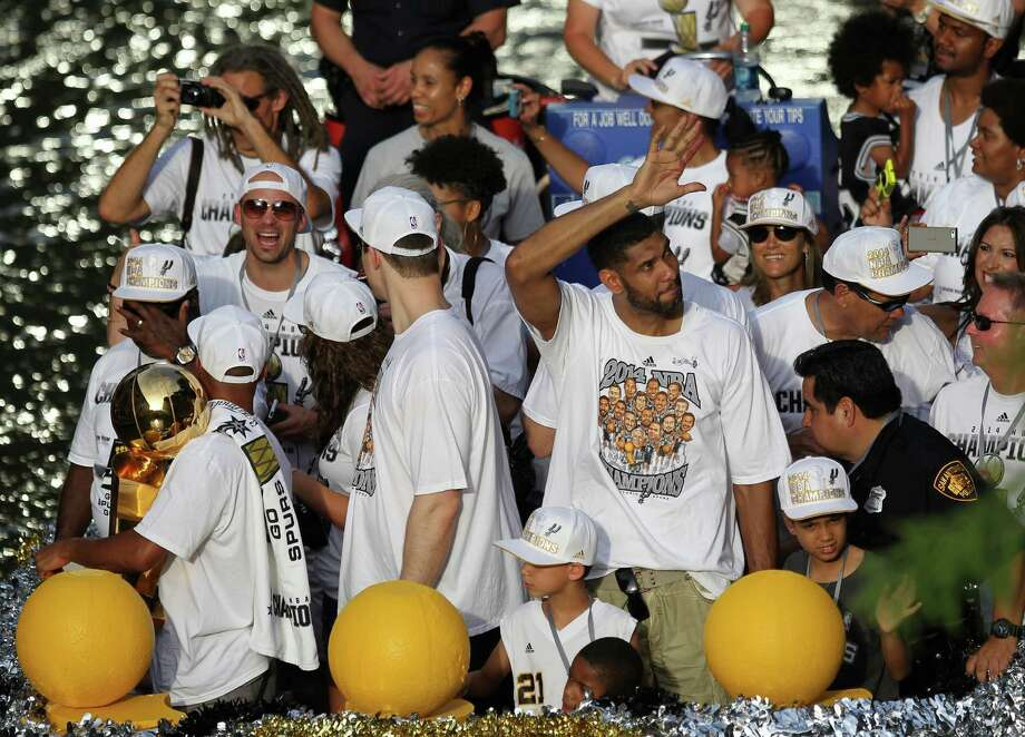 San Antonio Spurs' Tim Duncan, center, waves to the crowd during the river parade on Wednesday, June 18, 2014, on the San Antonio River. Photo: Timothy Tai, San Antonio Express-News / © 2014 San Antonio Express-News