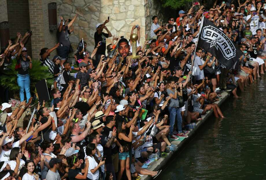 Spurs fans line the San Antonio River next to the Greater San Antonio Chamber of Commerce building to watch the river parade on Wednesday, June 18, 2014. Photo: Timothy Tai, San Antonio Express-News / © 2014 San Antonio Express-News