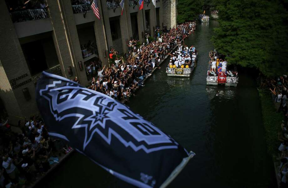 Floats pass on the San Antonio River next to the Greater San Antonio Chamber of Commerce building as fans cheer during the river parade on Wednesday, June 18, 2014. Photo: Timothy Tai, San Antonio Express-News / © 2014 San Antonio Express-News