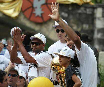 San Antonio Spurs' Tim Duncan waves to the crowd while joined by teammates Patty Mills and Aron Baynes during a parade River parade for the Spurs after the team capture their fifth NBA championship on Wednesday, June 18, 2014. Sitting beside Duncan was his daughter, Sydney. Photo: Kin Man Hui, San Antonio Express-News / ©2014 San Antonio Express-News